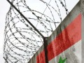 Barbwire and grey wall with Syria national flag © Valeriy - Fotolia