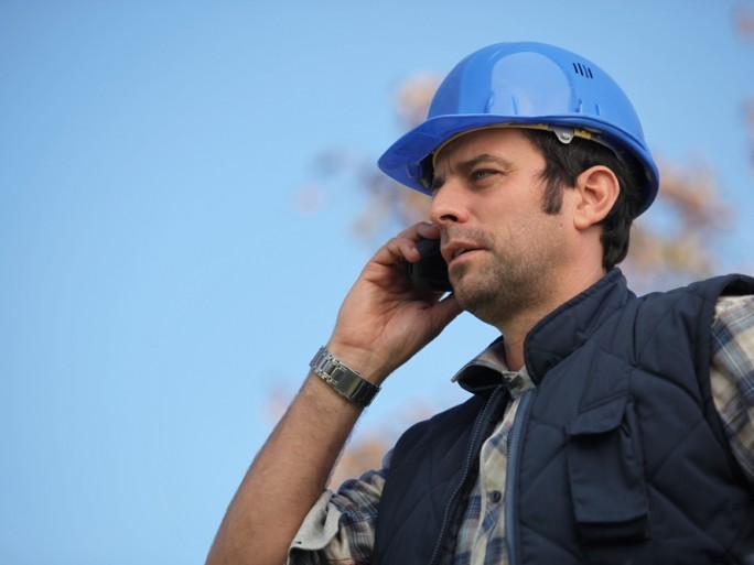 Mobile phone safety worker hard hat © auremar Shutterstock