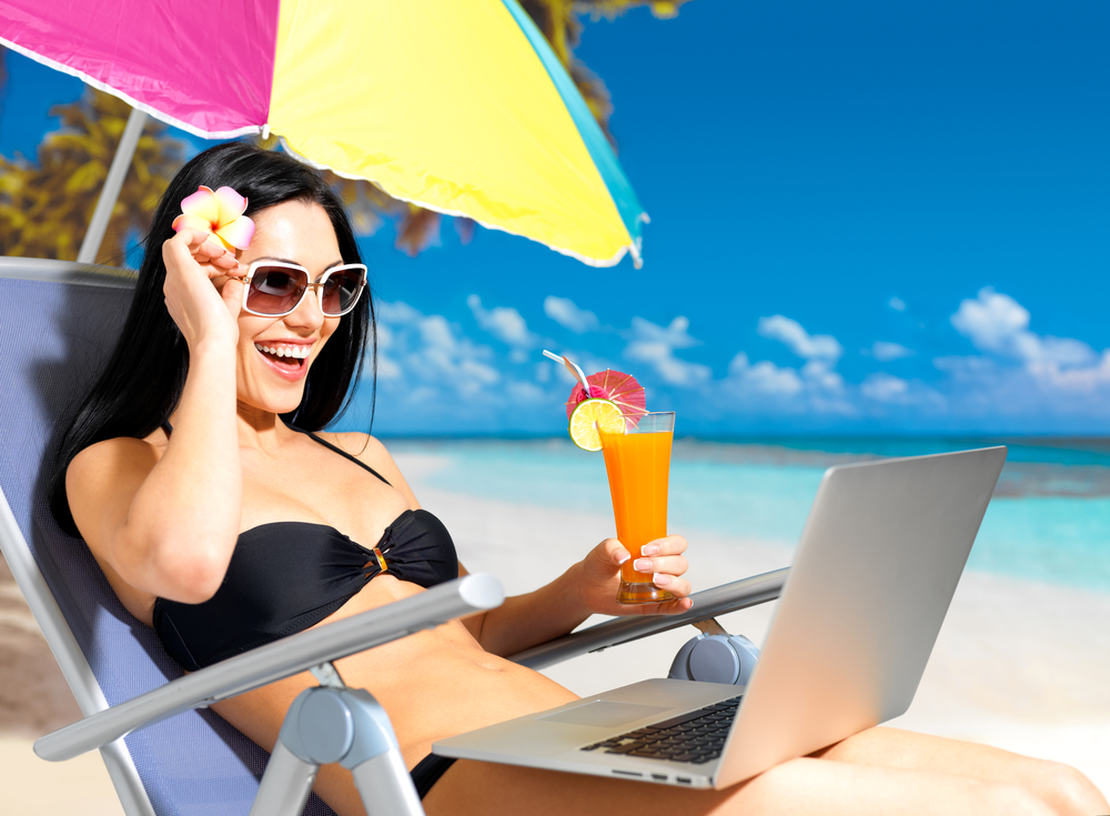 woman using laptop on beach holiday